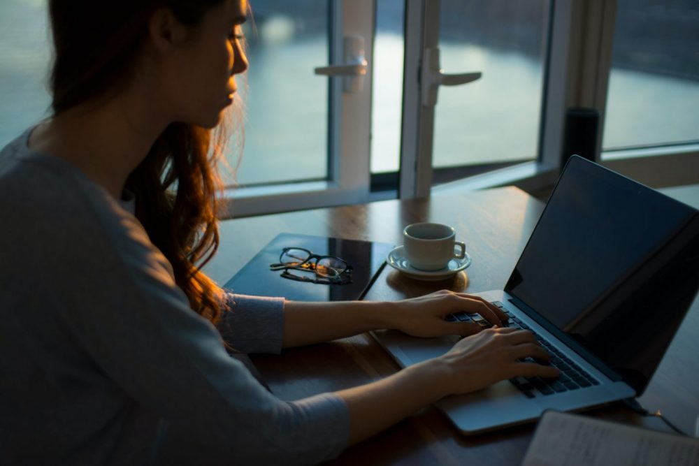 Woman at sunrise at a laptop
